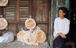 Elderly woman selling rice cakes Stock Images