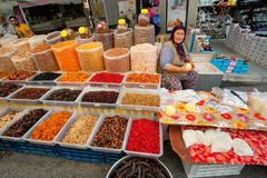 Elderly woman sells dried fruit and cottage cheese on rustic street market Royalty Free Stock Image