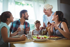 Elderly woman  serving meal to her family Stock Photos