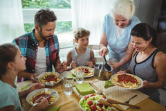 Elderly woman  serving meal to her family Royalty Free Stock Photography