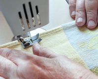 An elderly woman sew on a typewriter Stock Photo