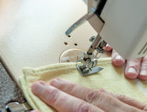 An elderly woman sew on a typewriter Stock Photography
