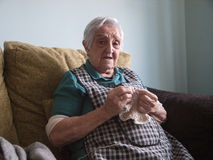 Elderly woman sewing at home Stock Photo