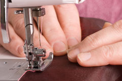 Elderly woman sews on the sewing machine Stock Images