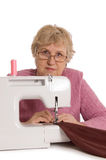 The elderly woman sews on the sewing machine. On white Royalty Free Stock Images