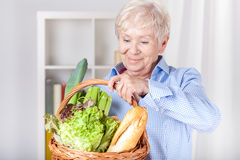 Elderly woman with shopping basket. At home Stock Images