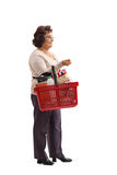 Elderly woman with a shopping basket waiting in line Royalty Free Stock Photo