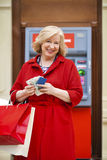 An elderly woman with shopping blonde is on the background in sh Stock Photography
