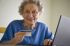 Elderly woman shopping online. Smiling senior woman using credit card and laptop Stock Photography
