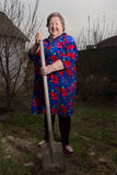 An elderly woman with a shovel. Royalty Free Stock Photography