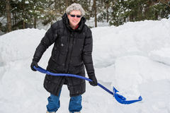 Elderly Woman Shoveling Snow. A portrait of a healthy elderly woman holding a shovel full of snow on a cold snowy day royalty free stock photos