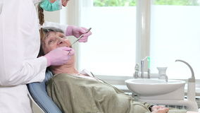 Elderly woman showing aching tooth to female dentist stock video