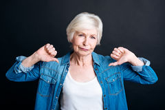 Elderly woman showing disapproval. I dont like it. Pleasant aged woman showign disapproval and lookign at you while standing on black background Royalty Free Stock Photography