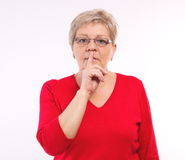 Elderly woman showing hand silence sign, emotions in old age Stock Photo