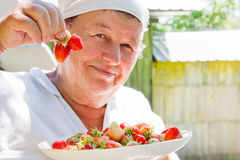 Elderly woman shows strawberry Royalty Free Stock Photography