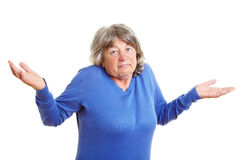 Elderly woman shrugging her. Clueless elderly woman shrugging with her shoulders Royalty Free Stock Photos