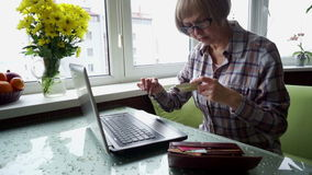 The elderly woman sick with rheumatoid arthritis using internet banking in home. stock footage