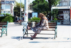 Elderly woman sits alone on bench Royalty Free Stock Photos