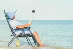 An elderly woman sits on the beach on a chaise longue, drinking wine and making photo against the background of the sea. An elderly woman sits on the beach stock photos