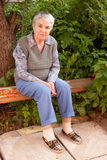An elderly woman sits on a bench Royalty Free Stock Images