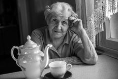 An elderly woman sits at the kitchen table near the kettle with tea. Royalty Free Stock Photos