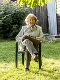 Elderly woman sits in the plastic chair in her garden Royalty Free Stock Photo