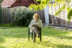 Elderly woman sits in the plastic chair in her garden Royalty Free Stock Images