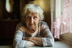 An elderly lone woman sits sadly near the window. stock photography
