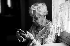 Elderly lone woman sits with smartphone in hands. Royalty Free Stock Photo