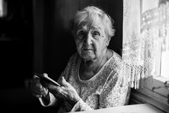 Elderly woman sits with smartphone in hands. Portrait. Stock Photography