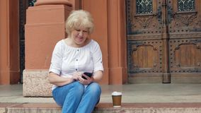 Elderly woman sits on the steps and using smartphone and drinking coffee. Vintage building in the background. stock video footage