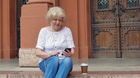 Elderly woman sits on the steps and using smartphone with earphones and drink coffee. Vintage building in the background. stock footage