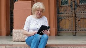 Elderly woman sits on the steps and using tablet computer with earphones. Vintage building in the background. Elderly woman sits on the steps and using tablet stock video footage
