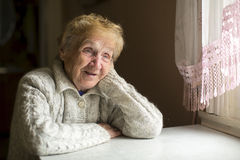 Elderly woman sits at a table near the window. Smile. Stock Photography
