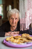 An elderly woman sits at a table with a rustic pastries. Happy. Stock Photo