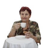Elderly woman sits at tea table Stock Images