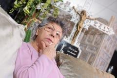 Elderly woman sitting alone in chapel rest Royalty Free Stock Image