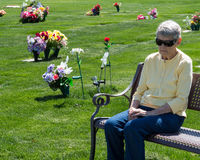 Elderly woman sitting on cemetery bench grieving. An elderly woman sitting on a cemetery bench amongst the graves in grief Royalty Free Stock Images