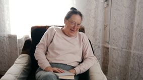 An elderly woman sitting in a chair, holding a book, laughing royalty free stock photography