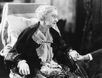 Elderly woman sitting in a chair holding a man's hand Stock Images