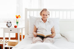 Elderly woman sitting comfortably in bed reading her favourite book Stock Photo