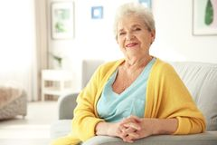 Elderly woman sitting on couch Stock Images
