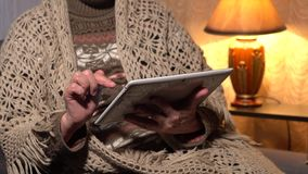 Elderly woman enjoys a tablet at home stock footage