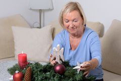 Elderly woman sitting decorating a Christmas tree Royalty Free Stock Photography