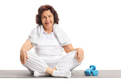 Elderly woman sitting on an exercise mat next to dumbbells stock photo