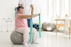 Elderly woman sitting on ball Stock Photo