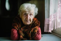 Elderly woman sitting in her house. royalty free stock image