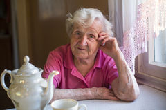 An elderly woman sitting in the kitchen. Portrait. Stock Image