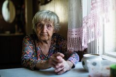 Elderly woman sitting in the kitchen. royalty free stock image