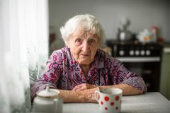 An elderly woman sitting at the kitchen table. Stock Image